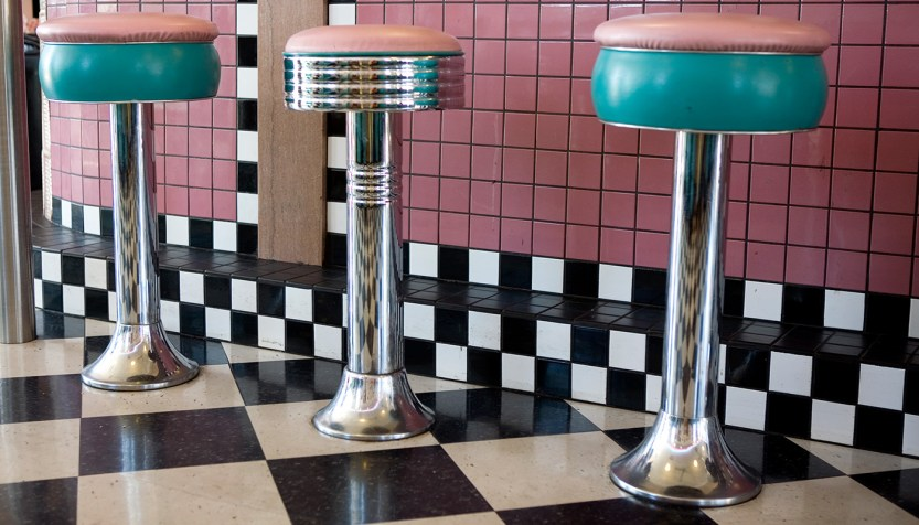 Pink and green bar stools in a retro diner