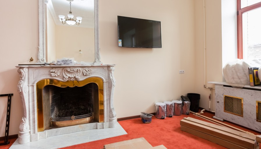 Older fire place with paint cans, and renovation supplies.