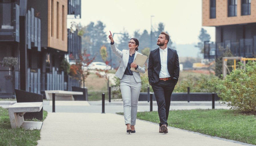A professional women and man walking down the sidewalk of a soon to be residential area.