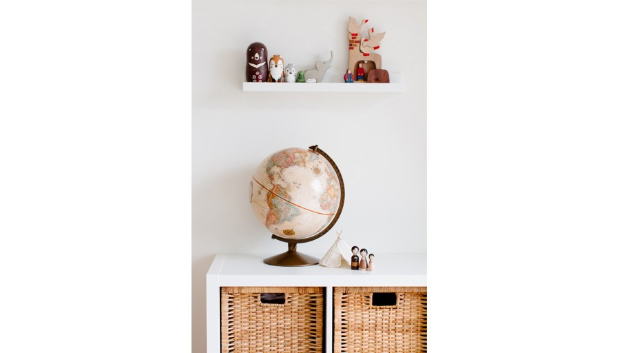 A globe on a shelf with a floating shelf with childs toys.
