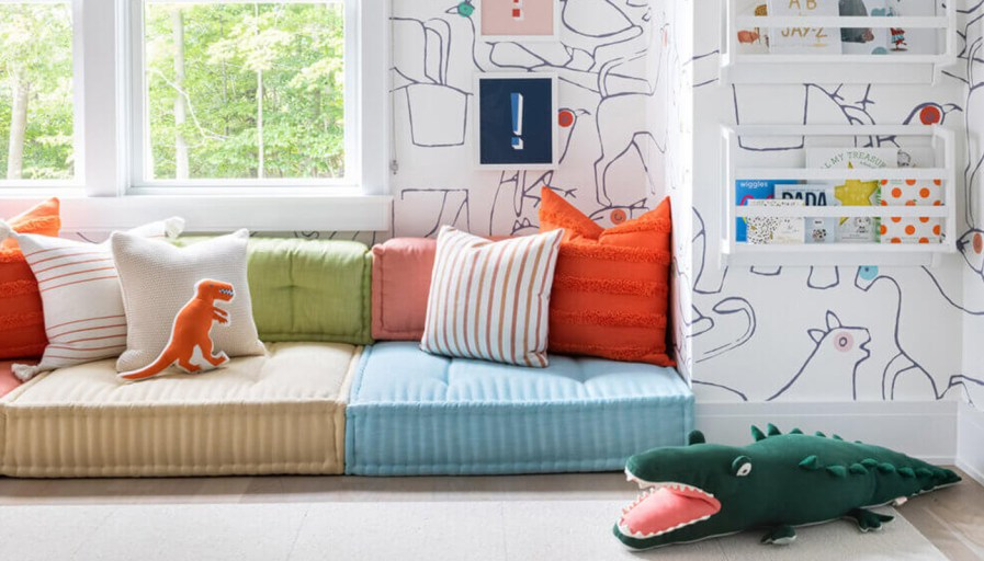 Large pillows on the floor, in a room that has colourful animal wallpaper.
