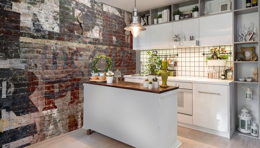 A brick mural wall, in a white kitchen.