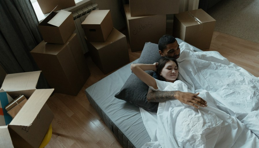 Couple sleeping on a mattress in a new home