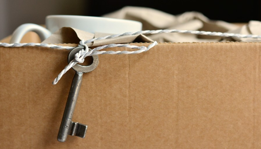 packed box with a key hanging from a string