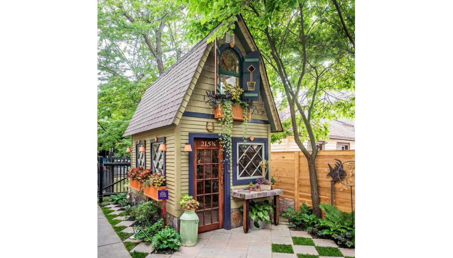 a tiny home shed that has been built in a backyard