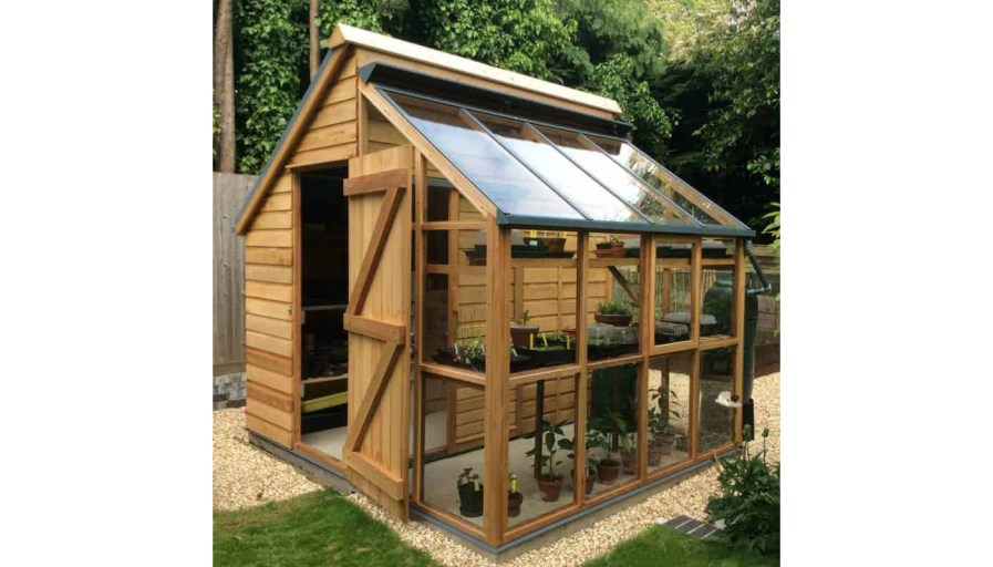 a shed that has been turned into a greenhouse with shelves and windows
