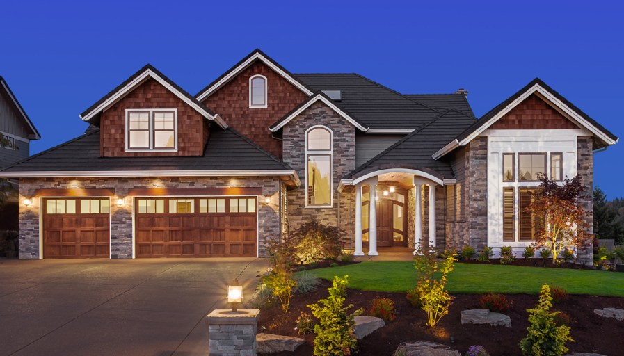 a large home with a stone driveway and landscaped yard