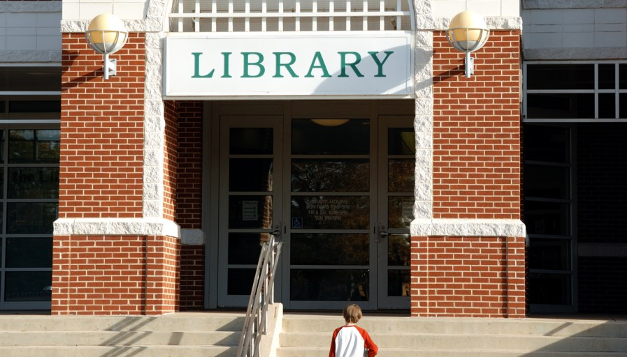 a child walking up concrete steps to a library