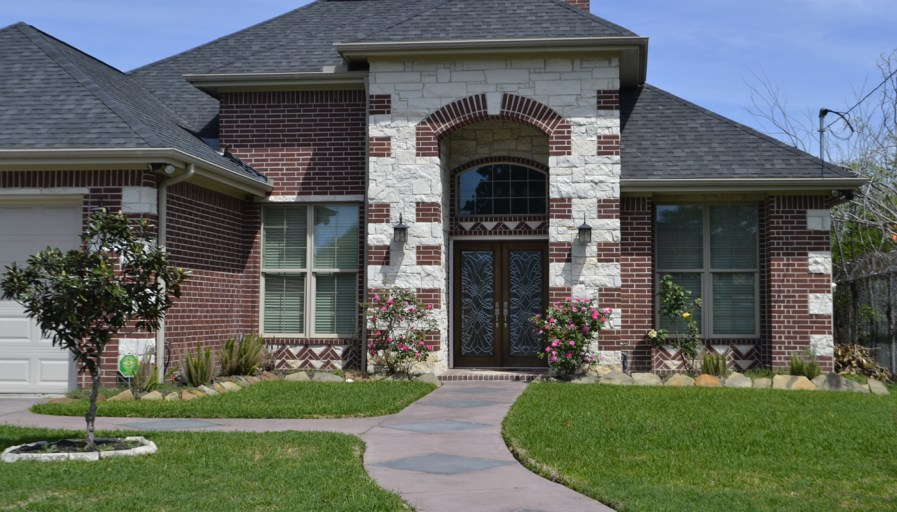a home with stone facade and stone pathway
