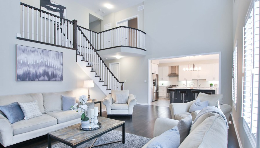a living room with light grey décor and a hardwood staircase