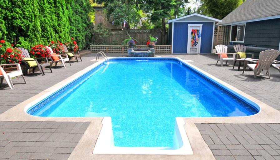 an interlocking brick pool deck around an in ground pool