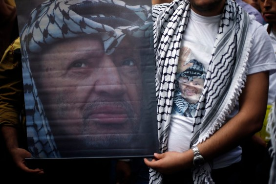 Palestinian Fatah supporters wear a T-shirt and hold a poster depicting late Palestinian leader Yasser Arafat during a rally marking the tenth anniversary of his death, in Gaza City