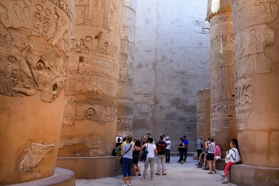 FILE - In this Sunday, Nov. 30, 2014, file photo, tourists point out the hieroglyphic on columns in the Hypostyle Hall at the Karnak Temple in Luxor, Egypt. Egyptian officials say a suicide bomber has blown himself up at the ancient temple of Karnak in Luxor, a southern city frequented by millions of foreign and Egyptian tourists every year.  (AP Photo/Hassan Ammar, File)