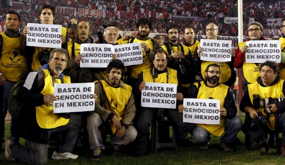 """Argentine photojournalists hold signs as they stage a protest against the murder of Mexican photojournalist Ruben Espinosa before the Copa Libertadores final soccer match between Argentina's River Plate and Mexico's Tigres in Buenos Aires August 5, 2015. The prominent Mexican news photographer was among five people found dead in a middle-class neighborhood of the capital on Friday, the city's prosecutor said on Sunday. Espinosa, who a month ago claimed in interviews that he felt threatened by the governor of eastern Veracruz state, was the lone male among five victims that police discovered bound and shot in the head in the capital's Narvarte neighborhood. The sign reads """"Enough of genocide in Mexico"""".  REUTERS/Marcos Brindicci"""