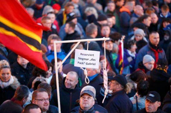 People hold up a mock hangman's gallows with a sign reading 'Reserved for Sigmar Gabriel' as they gather for an anti-immigration demonstration organised by rightwing movement Patriotic Europeans Against the Islamisation of the West (PEGIDA) in front of the Palace Church in Dresden, Germany October 12, 2015.  Sigmar Gabriel is the German minister of Economy.    REUTERS/Hannibal Hanschke