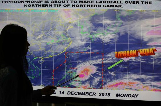 epaselect epa05068413 Filipino weather forecaster Loriedin de la Cruz shows the path of typhoon Melor, locally known as Nona at the Philippine Atmospheric Geophysical and Astronomical Services Administration (PAGASA) state weather bureau in Quezon city, northeast of Manila, Philippines, 14 December 2015. Severe Tropical Storm Melor continues to gain strength as it makes landfall at the Samar island and Bicol area, according to PAGASA . President Benigno Aquino III has ordered all concerned agencies to prepare local communities that will be affected by typhoon Melor.  EPA/MARK R. CRISTINO