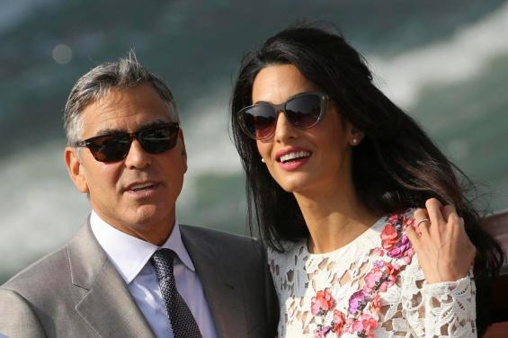 U.S. actor George Clooney and his wife Amal Alamuddin travel on a water taxi at the Grand Canal in Venice