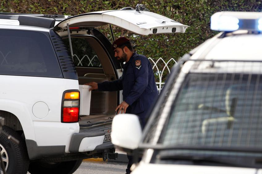 Police inspect cars at a checkpoint, during a manhunt for prisoners that escaped from Muharraq jail, in Manama
