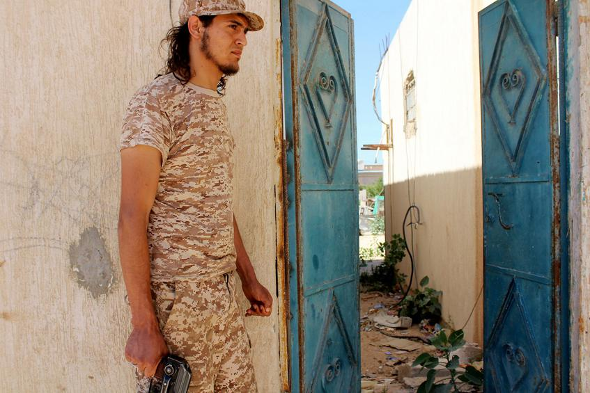 A fighter from forces aligned with Libya's new unity government stands in front of a house which has been cleared in the Zaafran area in Sirte