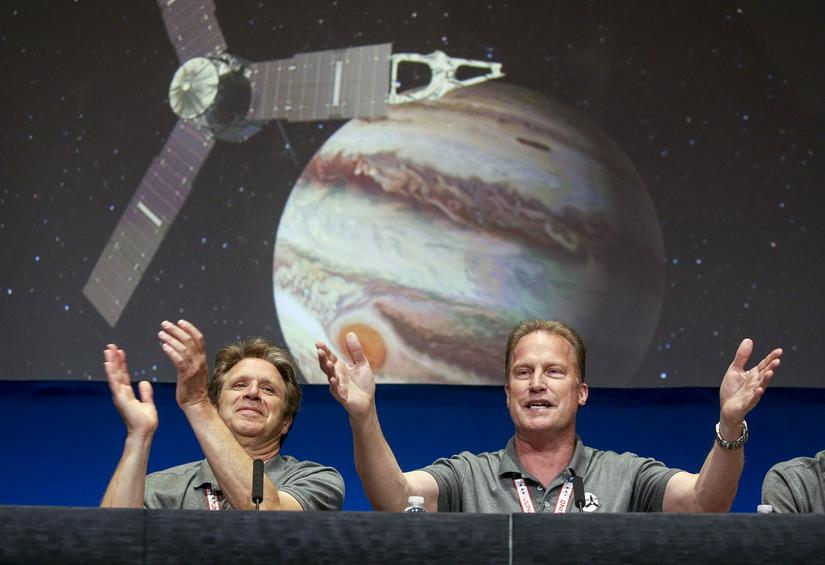 Scott Bolton, left, and Rick Nybakken are seen in a post-orbit insertion briefing at NASA's Jet Propulsion Laboratory following the solar-powered Juno spacecraft entered orbit around Jupiter on Monday, July 4, 2016, in Pasadena, Calif. (AP Photo/Ringo H.W. Chiu)
