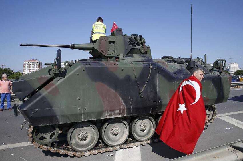 A man wrapped in a Turkisf flag walks past a military vehicle in front of Sabiha Airport, in Istanbul