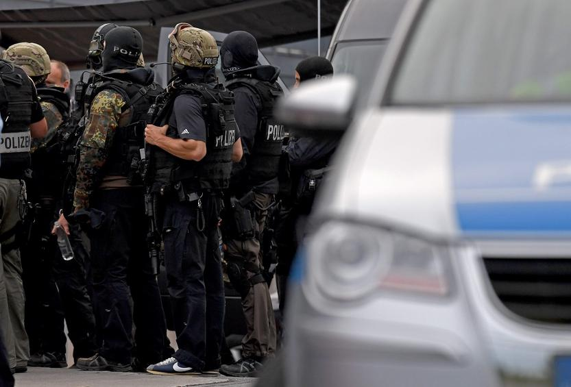 epa05444124 Police officers stand outside the 'Weserpark' shopping center in Bremen, Germany, 27 July 2016. The center was evacuated whilst authorities carried out a search for a 19-year-old suspect, who reportedly fled a psychiatric facility and may have links to Islamist extremists, according to German newspaper reports.  EPA/Ingo Wagner