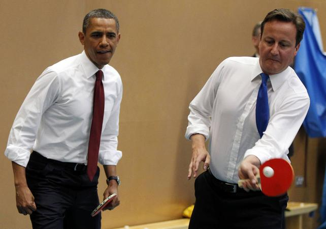 U.S. President Barack Obama plays table tennis against students with British Prime Minister David Cameron in London