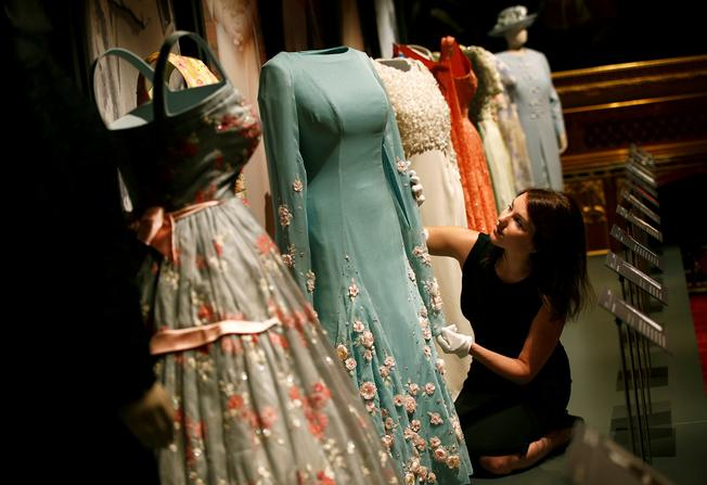 A member of staff of the Royal Collection poses with dresses worn by Britain's Queen Elizabeth, at Windsor Castle in Windsor