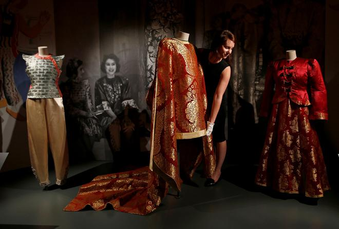A member of staff of the Royal Collection poses with pantomime outfits worn by Britain's Queen Elizabeth and Princess Margaret, at Windsor Castle in Windsor