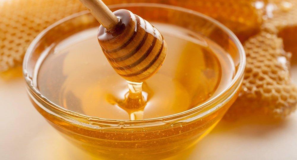 يتدفق العسل من ملعقة خشبية