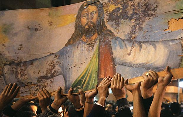 SANGUE DERRAMADO Cristãos coptas, do Egito, carregam uma imagem de Jesus Cristo manchada de sangue, em ato contra a violência de extremistas islâmicos  (Foto: Asmaa Waguih/Reuters)