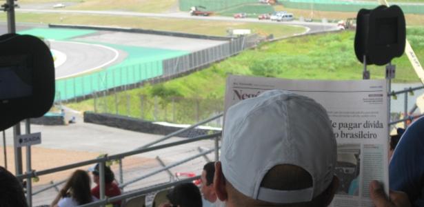 Torcedor lê jornal durante treino do GP do Brasil neste sábado, em Interlagos