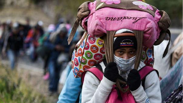 Una mujer migrante venezolana que se dirige a Perú carga bolsas mientras camina por la carretera Panamericana en Tulcán, Ecuador, después de cruzar desde Colombia, el último 21 de agosto.