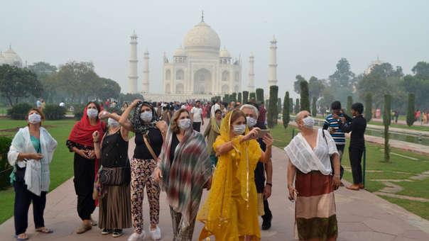 Un grupo de turistas extranjeros utilizan máscaras faciales durante su visita al Taj Mahal ante las condiciones de smog, en Agra.
