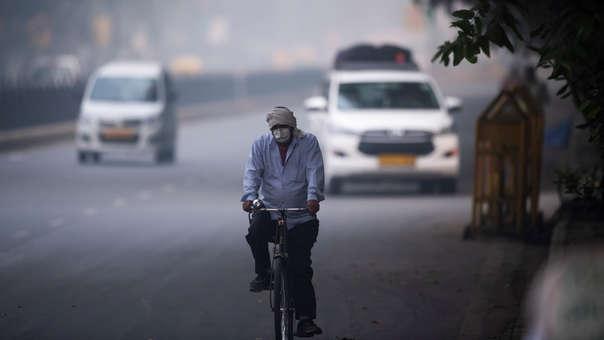In hombre utiliza una másca facial mientras maneja una bicicleta en una calle cargada de smog en Nueva Delhi.