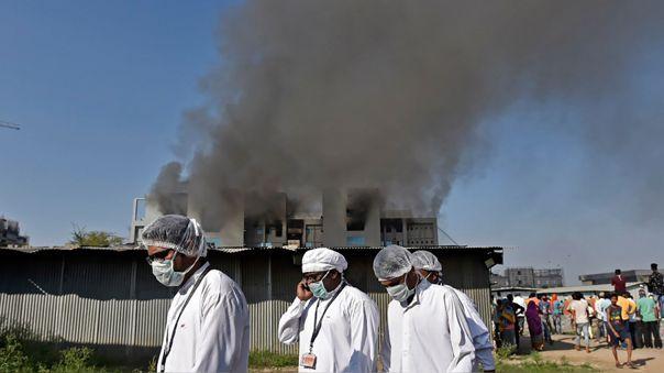 Los trabajadores con equipo de protección caminan después de que estalló un incendio en el Serum Institute de India en Pune.