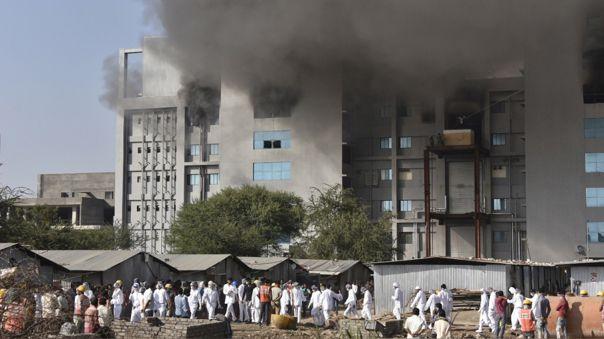 Los trabajadores indios se encuentran fuera de un edificio de la planta de Pune del Serum Institute of India, fabricante de vacunas de Covid, después de que estallara un incendio en Pune.