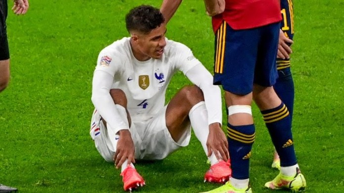 Raphael Varane sits on the pitch after an injury during the Nations League final - Miguel Medina/Pool Photo via AP