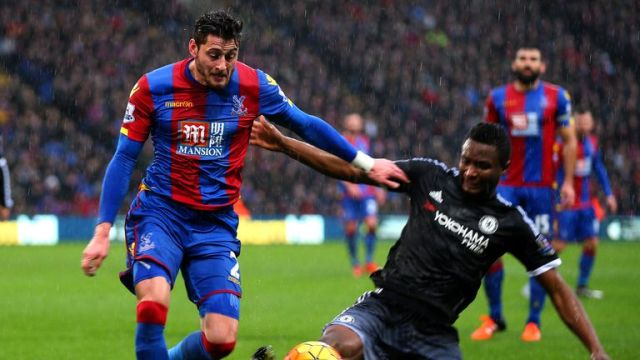 Joel Ward battles for the ball with John Obi Mikel in difficult conditions