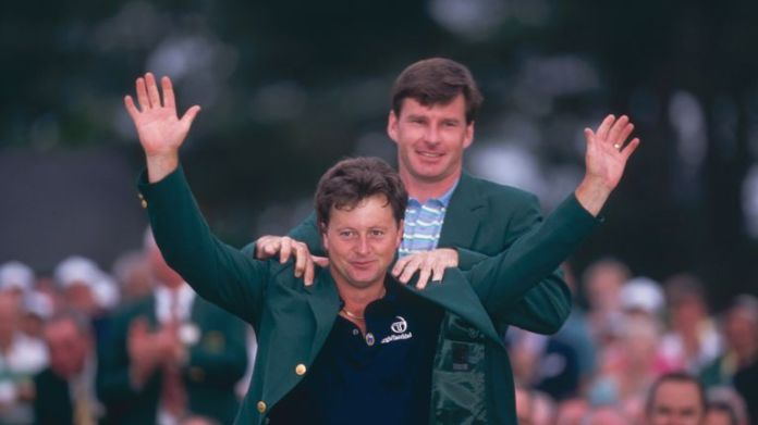 Woosnam receives the green jacket from Nick Faldo