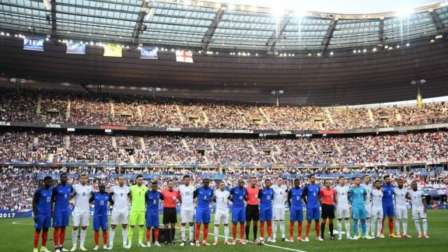 England and French players stand together at the Stade De France
