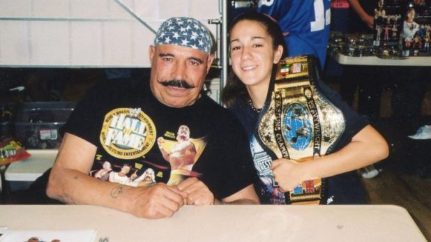 Bayley - predicting her future world championship reigns with a replica belt - meets former WWF world champ the Iron Sheik