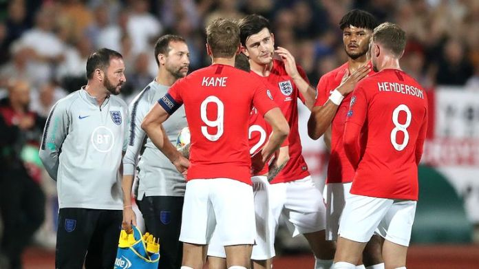 England players talk amongst themselves during a temporary break in play following racist chanting from a section of the home support