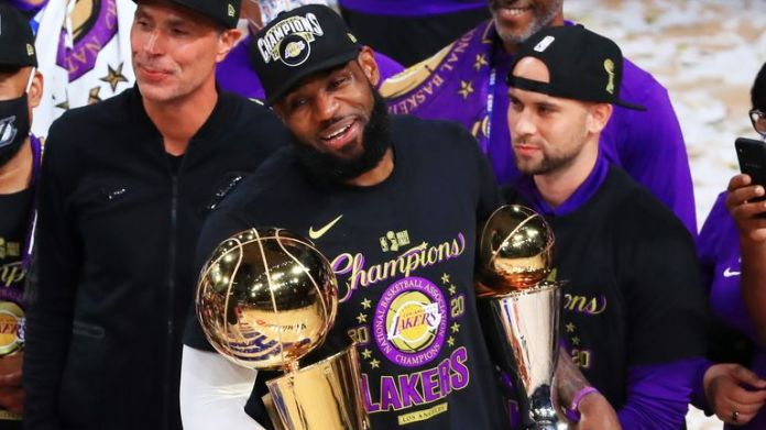 LeBron James holds the NBA Championship and MVP Finals trophies after the Lakers'  Game 6 win