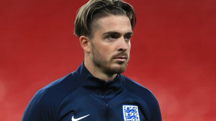 England's Jack Grealish (R) watches during the national anthems during the International Friendly match between England and Republic of Ireland at Wembley Stadium on November 12, 2020 in London, England.  Sports stadiums in the UK remain under strict restrictions due to the coronavirus pandemic, as government social distancing laws ban fans inside venues, resulting in closed-door matches.  (Photo by Mike Egerton - Pool / Getty Images)