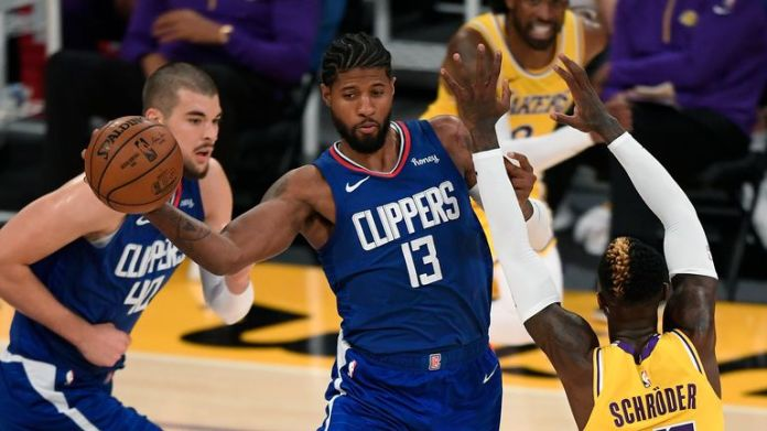 Paul George #13 of the LA Clippers passes around Dennis Schroder #17 of the Los Angeles Lakers during the season opening game at Staples Center on December 22, 2020
