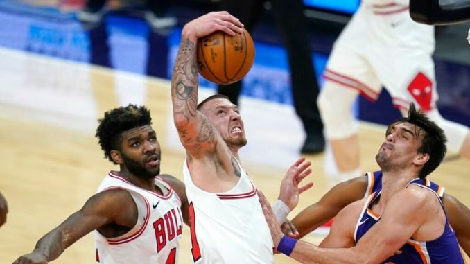 AP - Chicago Bulls center Daniel Theis, middle, pulls down a rebound as Phoenix Suns forward Dario Saric, right, and Bulls forward Patrick Williams