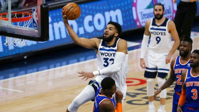 AP - Minnesota Timberwolves' Karl-Anthony Towns (32) shoots over ' RJ Barrett (9)
