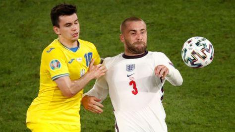 Ukraine's Mykola Shaparenko, left, is challenged by England's Luke Shaw