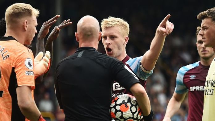 Ben Mee confronts referee Anthony Taylor after a penalty for Burnley is overturned